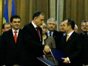 Presedintele PSD, Mircea Geoana (S), dă mâna cu preşedintele PD-L, Emil Boc (D), după semnarea Parteneriatului PD-L - PSD pentru România. Foto: MEDIAFAX
