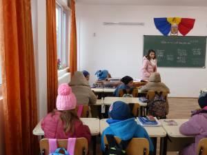 Elevii stau cu căciuli și geci în sălile de curs