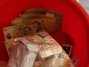Aproape două milioane de euro ascunși inclusiv în găleți, ridicați în dosarul de corupție de la Serviciul de Permise și Înmatriculări
